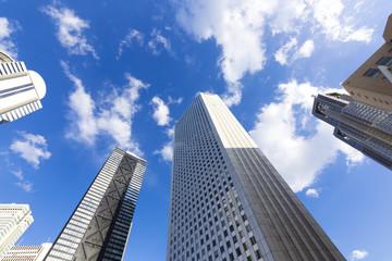 快晴 青空 超広角で見上げる新宿高層ビル群 東京都庁のツインタワーから差す太陽
