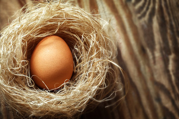 Eggs in the nest on old wooden table background, top view