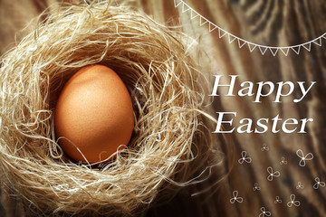 Happy easter egg in the nest on wooden background