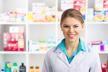 Young salesperson in drug store posing over medicines background