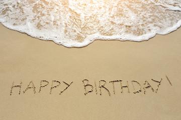 happy birthday written on sand beach