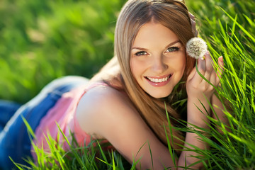 Beautiful woman are relaxing in a spring green field
