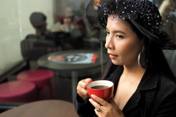 Asian woman with cup of coffee