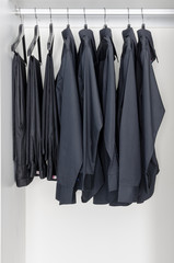 row of black shirts and pants hanging on coat hanger