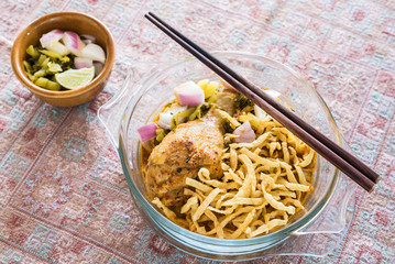 Thai northern curry noodle with chicken in glass bowl