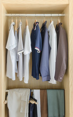 wooden closet with clothes hanging