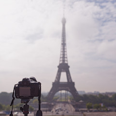 Camera on tripod pointing Eiffel Tower in Paris, France.