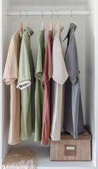 colorful shirts hanging in white wardrobe
