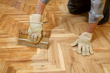 Obraz Varnishing of oak parquet floor, workers hand and tool - fototapety do salonu