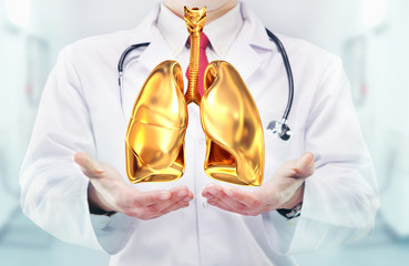 Doctor with stethoscope and golden lungs on the  hands