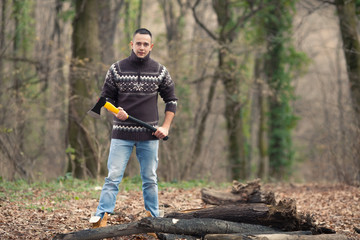 Young lumberjack holding an axe preparing to cut the tree