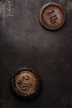 1 and 2 lb pound vintage iron weight on metal backdrop