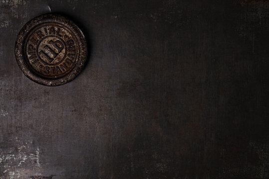 1lb pound vintage iron weight on metal backdrop