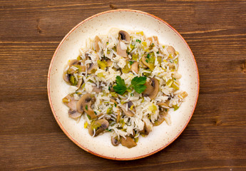 Risotto with mushrooms on wooden table seen from above