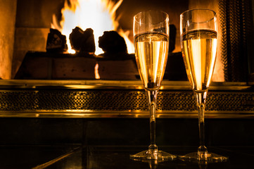 Two glasses of champagne in front of a romantic fire