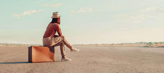 Traveler girl sitting on a suitcase on road