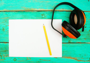 Paper with pencil and working tools on wooden, green background.