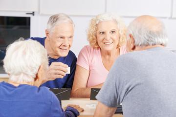 Gruppe Senioren beim Spielen von Rummy im Altenheim