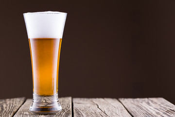 Beer glass in a golden background.