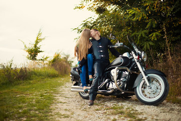 Young couple kiss in mirror on beautiful bike on road.