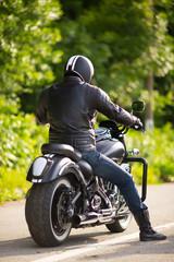 biker in mask sitting unknown on big chopper bike on road