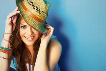 woman with toothy smile touching hat