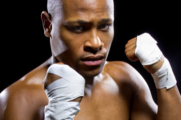 black mma fighter or boxer posing and flexing muscles
