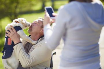 Frau macht Foto von Mann mit Hundewelpe im Rollstuhl