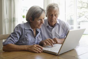 Deutschland, Bayern, älteres Paar mit Laptop zu Hause