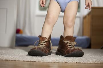 Kleinkind in den Schuhen des Vaters
