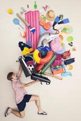 Deutschland, künstliche Szene Mann öffnet Gepäck voller Spielzeug für den Strand