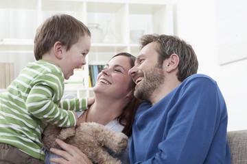 Deutschland, Bayern, München, Eltern spielen mit Jungen (2-3 Jahre) im Wohnzimmer