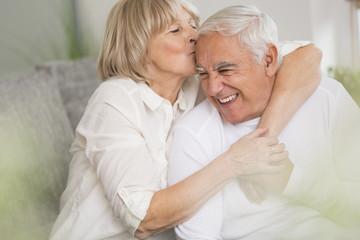 Ältere Frau küsst ihren Mann im Wohnzimmer