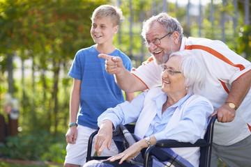 Großvater und Enkel mit Großmutter im Rollstuhl