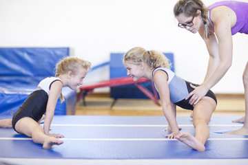 Trainer mit zwei Mädchen, Turnen üben auf dem Boden