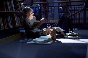 Studentin auf dem Boden liegend in einer Bibliothek, Freund liest ein Buch