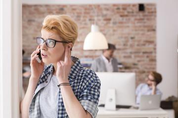 Ernste junge Frau am Handy im Büro