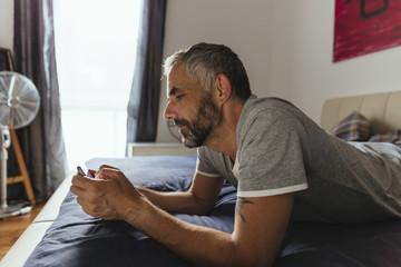 Mann liegt auf seinem Bett mit seinem Smartphone