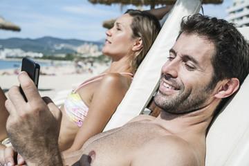 Spanien, Paar mittleren Alters entspannt auf Liegestuhl