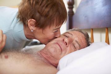 Ältere Frau küsst kranken Mann im Bett