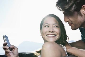 Spanien, Mallorca, Junges Paar mit Handy im Cabrio, close up