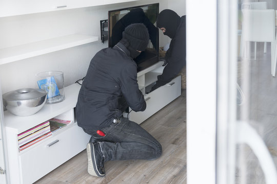 Two burglars at work in an one-family house at daytime