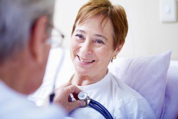 Doktor, der ältere Frau im Krankenhaus untersucht