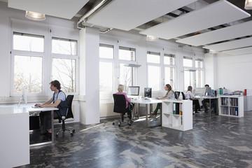 Deutschland, Bayern, München, Männer und Frauen arbeiten am Computer im Büro