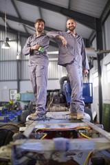 Zwei lächelnde Mechaniker in der Fabrik