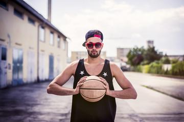 Portrait des jungen Mannes mit Basketball, Basecap und Sonnenbrille