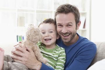 Deutschland, Bayern, München, Vater und Sohn (2-3 Jahre) mit Teddybär, Portrait, Lächeln