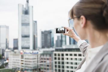 Deutschland, Hessen, Frankfurt am Main, Frau, die ein Bild von der Skyline mit ihrem Smartphone macht