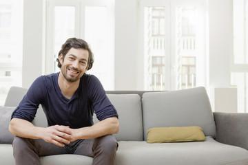 Lächelnder Mann sitzt auf dem Sofa