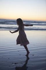 Kleines Mädchen am Strand, tanzen in der Abenddämmerung